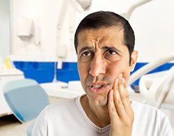 A middle-aged man holding his cheek while in pain because of a dental emergency in Coatesville
