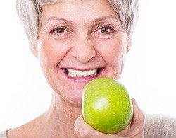 Smiling older woman eating an apple