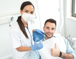 A younger man and his female dentist giving a thumbs up after undergoing a smile makeover