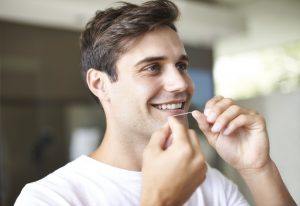 Young man flossing teeth