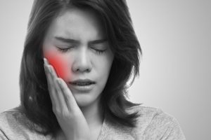 a young woman with braces holding her cheek in pain because of a dental emergency
