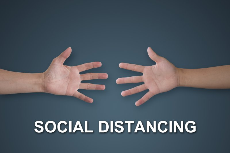 "two hands reaching for each other with the words ""social distancing"" underneath"
