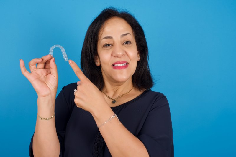 older woman pointing to her Invisalign aligner